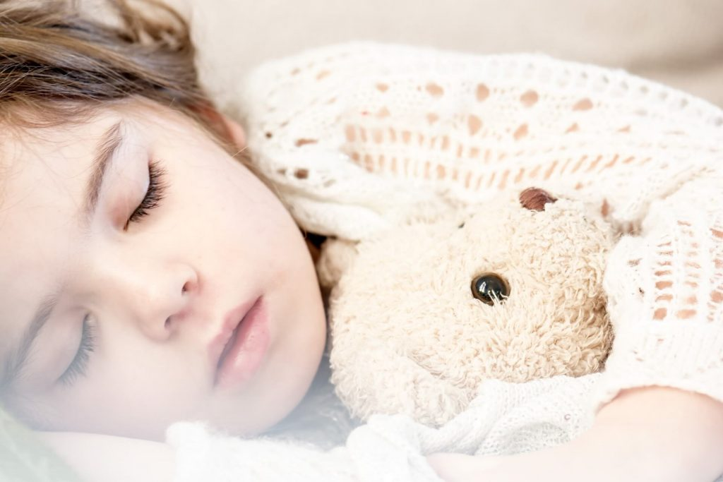 a sleeping child hugging a soft toy